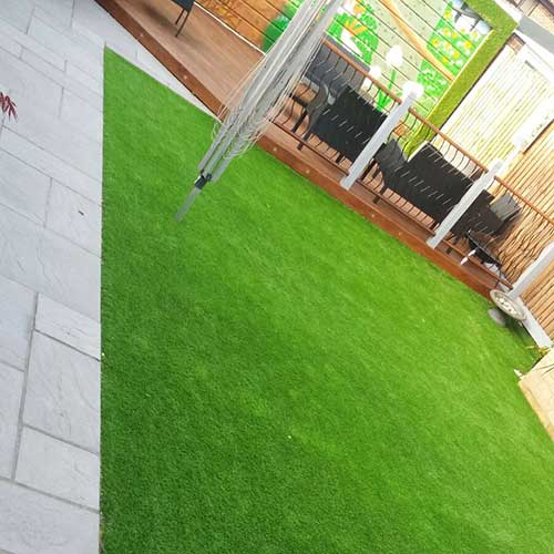 Artificial grass fitter next to pathway and decking